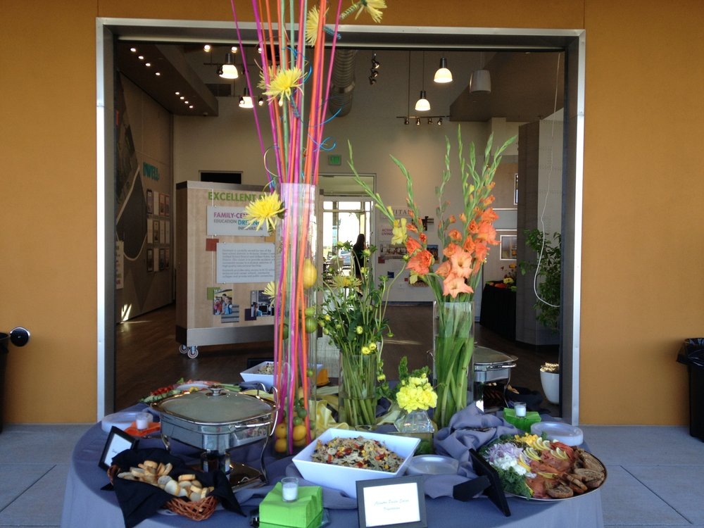 Catered event table with plates of food and two vases of flowers Phoenix AZ